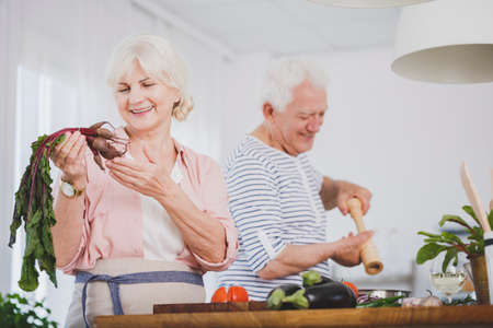 Senior woman holding a small beetroot and an older man seasoning food, preparing a healthy vegan meal together