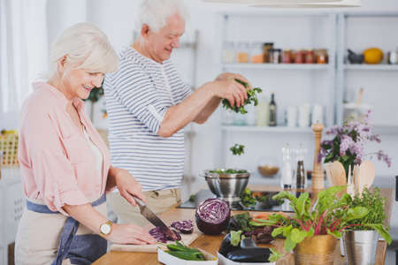 Happy elderly woman chopping vegetables and her husband tossing kale, preparing a healthy meal together