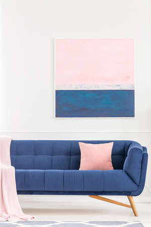 Pink pillow on navy blue sofa against white wall with painting in pastel living room interior
