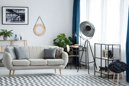 Industrial lamp next to beige settee in living room interior with patterned carpet and poster Stock Photo