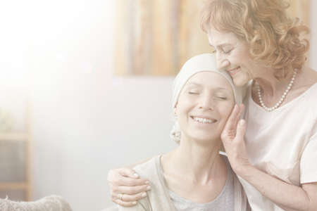 Bright photo with flare effect showing mother and daughter with cancer hugging and smiling Stock Photo