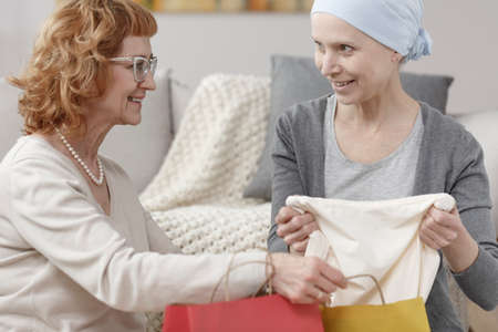 Happy mother giving clothes to her daughter during home visit before cancer operation Stock Photo