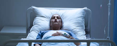 Suffering senior woman with cancer lying in hospital bed