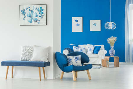 Velvet bench against white wall with floral poster in blue living room interior with white sofa