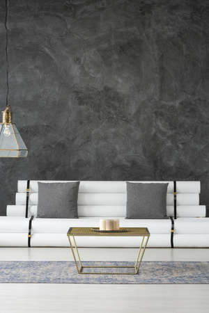 Elegant room with recycled sofa, golden, metal coffee table and a diamond ceiling lamp in a gray designer interior with copy space