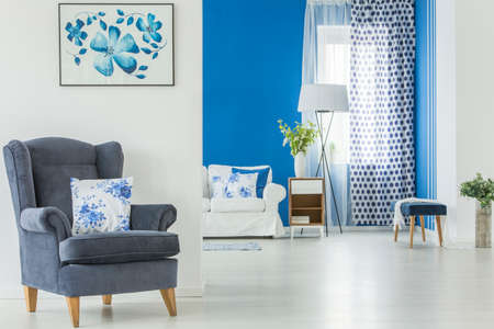 White cushion with floral pattern on blue armchair standing against white wall in spacious living room interior