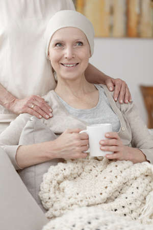 Happy lady with cancer wearing a headscarf resting on a sofa with blanket and tea mug