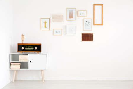 食器棚に白、空の壁とヴィンテージラジオ上の写真ギャラリーとリビングルームのインテリアでミニマリズム 写真素材