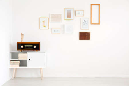 Minimalism in living room interior with pictures gallery on white, empty wall and vintage radio on cupboard