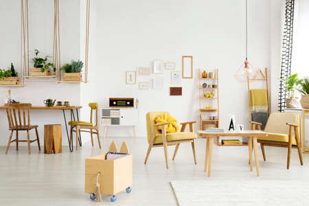 Spacious dining room interior with wooden crates on swings and yellow armchairs in the relax area Stock Photo