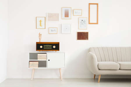 Radio on white cupboard standing next to a comfy sofa in bright living room interior with pictures gallery