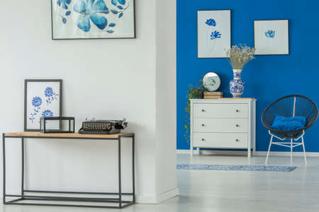 White, wooden chest of drawers standing against a navy blue wall in floral living room interior