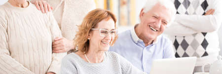 Smiling senior couple using a laptop during classes at university of the third age Stock Photo