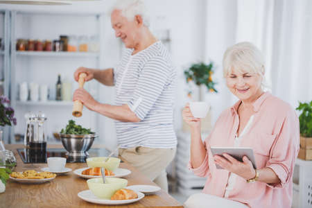 Senior woman reading a digital newspaper on a tablet in the kitchen and her husband preparing a salad