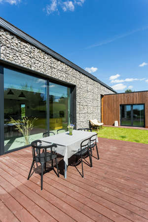 Wooden terrace with garden furniture placed at the back of stone house