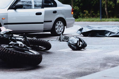 Car and motorbike crash site with a helmet lying in the middle of the street