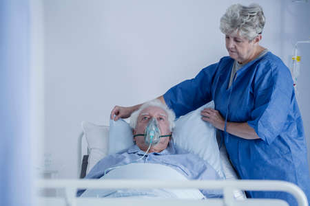 Lady in a blue apron adjusting her husbands pillow in a hospice