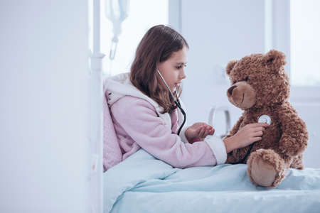 Little girl playing doctor and examining a teddy bear with stethoscope at the hospital