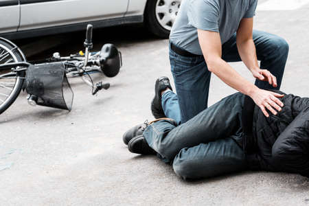 Pedestrian helping a victim of an automobile accident lying on the street next to a broken bike