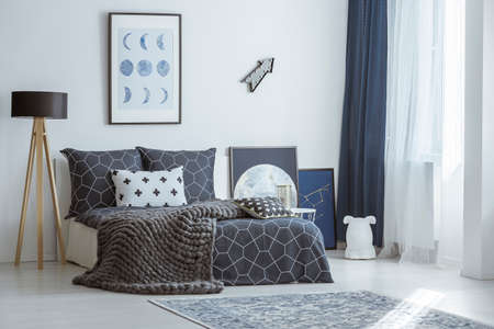 Arrow and poster on the wall above bed in bright bedroom interior with lamp and rug
