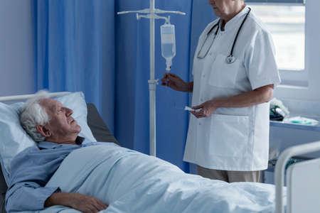 白い制服を着た医師が高齢患者の点滴を設定
