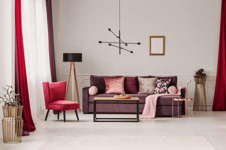 Lampe au-dessus de la table dans un intérieur de salon sophistiqué avec fauteuil rouge et canapé violet contre le mur avec une affiche