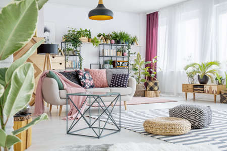 Poufs on striped carpet in spacious living room interior with plants and table next to sofa with pillows Stock Photo - 97751942