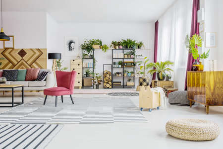 Pouf in spacious living room interior with red armchair next to sofa and plant on wooden cupboard