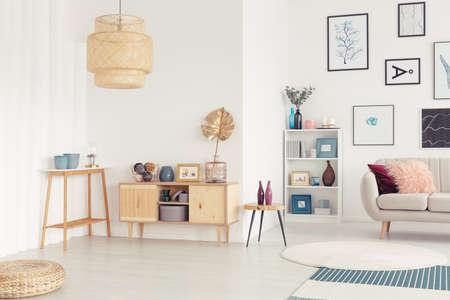 ギャラリー付きの自然なリビングルームのインテリアに金箔を持つ木製の食器棚の上にラタンランプ