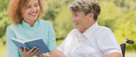 Smiling elderly woman reading a book with her nurse in the park Stockfoto