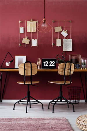 Wooden chairs at table with laptop against cherry wall with notes in workspace interior