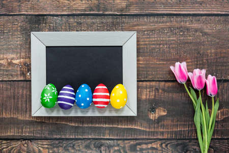 Colorful painted eggs on a black picture in white frame
