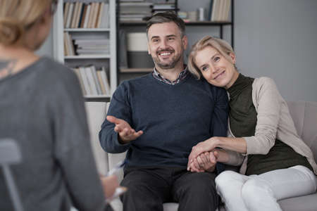 Middle-aged couple solving problems during marital therapy with a psychologist Stock Photo
