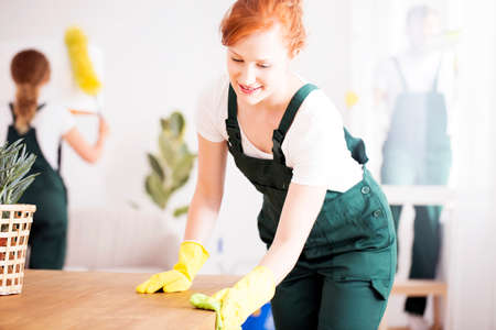 Young female worker from a cleaning company polishing a wooden table