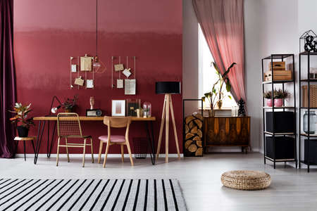 Striped carpet and pouf in spacious, red workspace interior with window and chairs at table