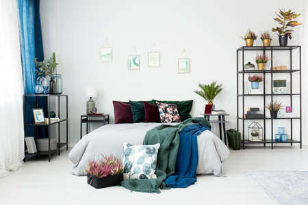 Vintage bedroom interior with plants and cushions with floral motifs on a cozy bed Archivio Fotografico - 97578695