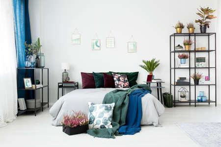 Vintage slaapkamerinterieur met planten en kussens met bloemmotieven op een gezellig bed