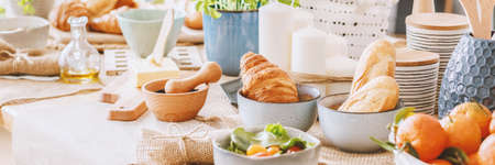 Croissant in a bowl next to mortar and pestle on dining table with butter and salad