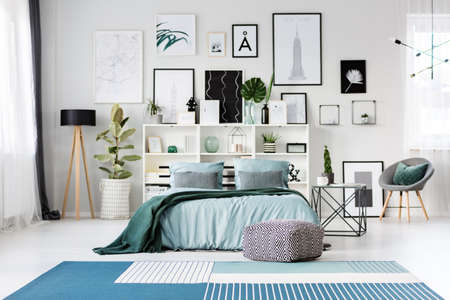 Patterned pouf in front of a bed with blue sheets in bright bedroom interior with posters gallery