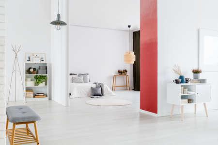 赤い壁の隣に食器棚と背景にベッドを持つアパートのインテリアの白い控え室の灰色のベンチ
