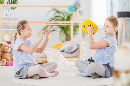 Smiling twin sisters playing with yellow plush dice in the classroom 版權商用圖片