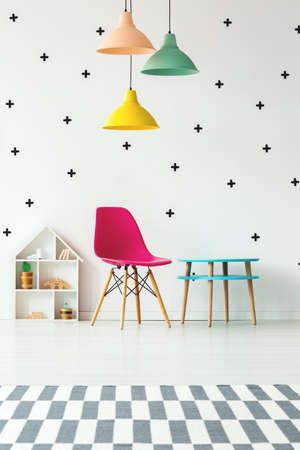 Pink chair, blue table and colorful lamps set on patterned wall in kid's room interior