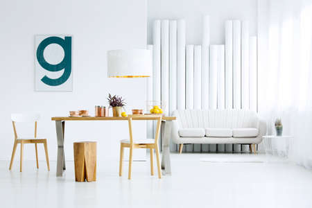 Wooden stool at table in dining room interior with poster on white wall and sofa