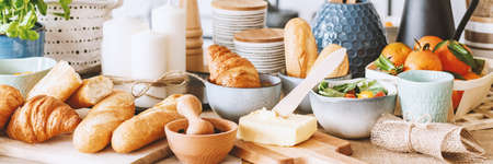 Panorama of croissant, bread and butter for breakfast on dining table with candles