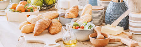 Olive oil between croissants, butter and mortar with pestle on dining table