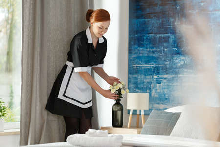 Maidservant putting flowers into a vase while cleaning hotel bedroom