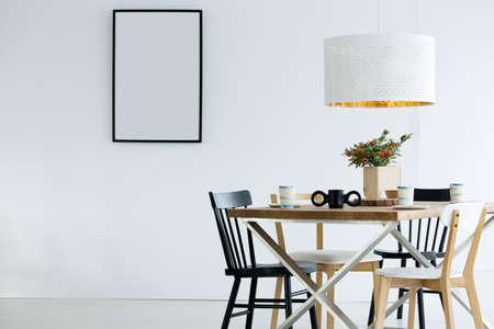 Maqueta de cartel vacío en el interior del comedor simple con lámpara blanca encima de la mesa con planta