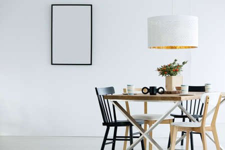 Mockup of empty poster in simple dining room interior with white lamp above table with plant Фото со стока