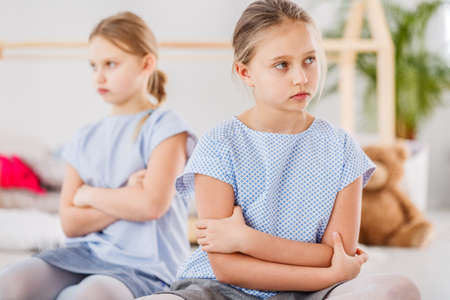 Sad young girl sitting alone after a quarrel with her twin sister