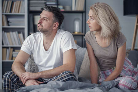 Middle-aged married couple sitting on a bed, having problems with communication